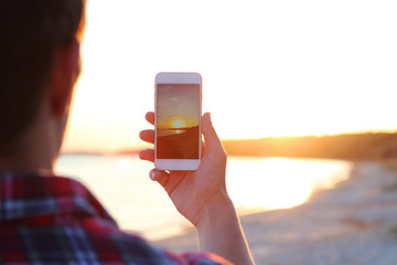 guy makes a photo on a modern smartphone on a sunset background by the sea