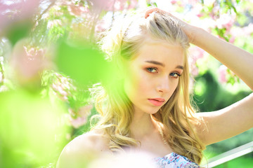 Beautiful young girl on background flowering cherry tree.