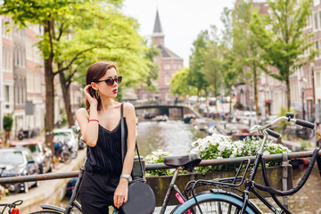 portrait of a beautiful fashionable young girl in the streets of Amsterdam, the Netherlands in the spring evening