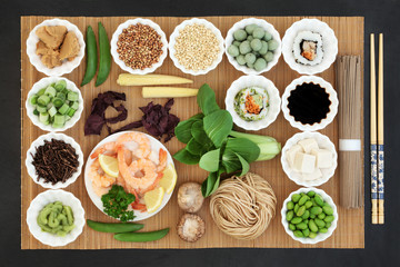 Macrobiotic Japanese food concept with seafood, sushi, miso and wasabi  paste & nuts, tofu, kuchika tea, vegetables, soba noodles, soy, tofu, with foods high in protein, antioxidants & vitamins.