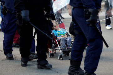 A girl sleeps in a stroller near riot police officers during a protest march at the G7 Summit in Quebec City