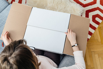 Woman unboxing cardboard box online e-commerce site delivery  - view from above in living room