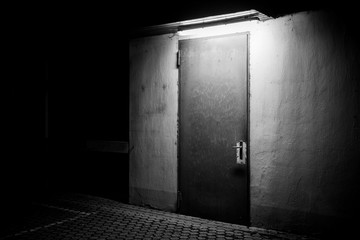 One door in the darkness illuminated from the above in empty city - black and white