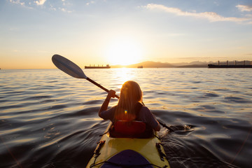 Woman on a kayak is paddeling in the ocean during a vibrant sunset. Taken in Vancouver, British Columbia, Canada. Concept: adventure, holiday, lifestyle, sport, recreation, activity, vacation