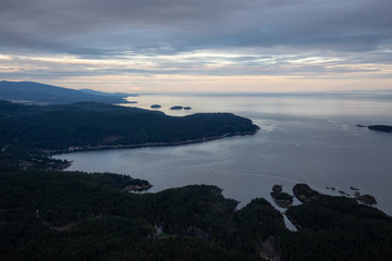 Aerial view of Sunshine Coast during a vibrant cloudy sunset. Located Northwest of Vancouver, British Columbia, Canada.