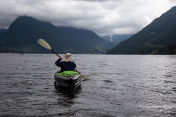 Adventurous Man on a Kayak is enjoying the beautiful Canadian Mountain Landscape. Taken in Jones Lake, near Chilliwack and Hope, East of Vancouver, BC, Canada.