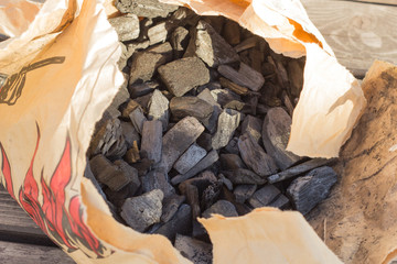 Black glossy coal for bonfire and bbq from supermarket inside a craft brown paper bag.