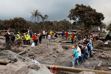 Residents pull a rope to remove debris and access a buried house, after the eruption of the Fuego volcano, at San Miguel Los Lotes