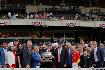 Owners Kenny Troutt and Teo Ah Khing, of the China Horse Club smile with jockey Mike Smith and trainer Bob Baffert with the Belmont Stakes trophy after Justify won the 150th running of the Belmont Stakes, the third leg of the Triple Crown of Thoroughbred R