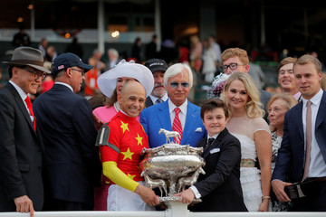 Owners Kenny Troutt (2nd L) and Teo Ah Khing, of the China Horse Club (L) smile with jockey Mike Smith, and trainer Bob Baffert and the Belmont Stakes trophy after Justify won the 150th running of the Belmont Stakes, the third leg of the Triple Crown of Th