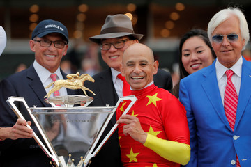 Owners Kenny Troutt (L) and Teo Ah Khing, of the China Horse Club (C) smile with jockey Mike Smith, and trainer Bob Baffert and the Triple Crown trophy after Justify won the 150th running of the Belmont Stakes, the third leg of the Triple Crown of Thorough