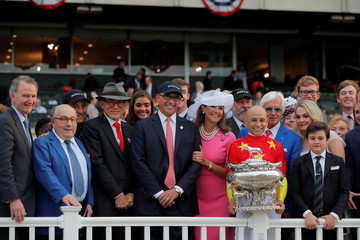 Owners Kenny Troutt (C) and Teo Ah Khing, of the China Horse Club (3rd L) smile with jockey Mike Smith, trainer Bob Baffert and the Belmont Stakes trophy after Justify won the 150th running of the Belmont Stakes, the third leg of the Triple Crown of Thorou