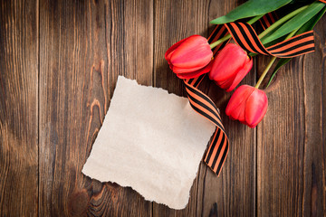 St. George ribbon, red tulips and paper greeting card on wooden background. Victory day or Fatherland defender day.