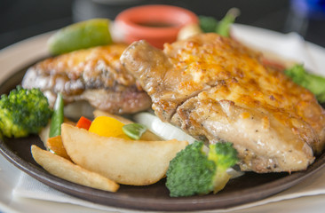 Baked potatoes with chicken steak egg and vegetable on a white plate
