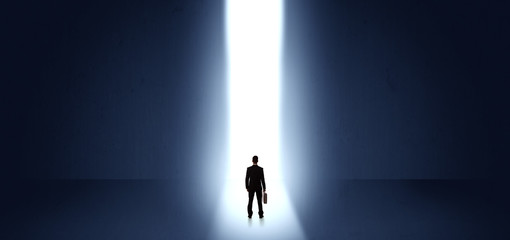 Businessman standing and seeing the light at the end of a big wall