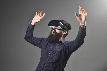 Emotional bearded man wears virtual reality goggles, gesturing with hands. Connection, future technology, new generation, progress concept. Virtual reality glasses, entertainment. Man using VR headset