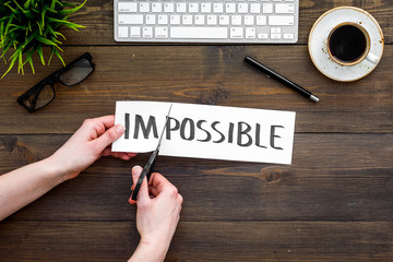 From impossible to possible. Do difficult task at work concept. Cutting the part im of written word impossible by sciccors. Office desk. Dark wooden background top view copy space