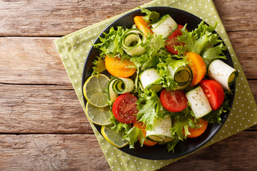 Organic salad of zucchini, tomatoes, lettuce and lime dressed with olive oil close-up on a plate. Horizontal top view