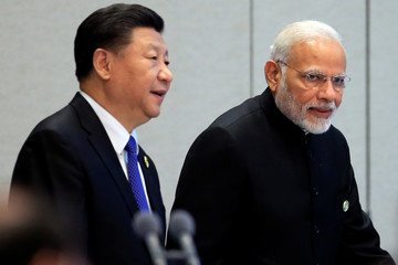 China's President Xi Jinping and India's Prime Minister Narendra Modi arrive for a signing ceremony during Shanghai Cooperation Organization (SCO) summit in Qingdao