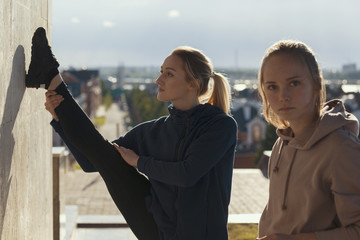 Two young attractive women doing acrobatics with cityscape on background