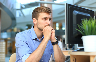 Young man sitting and looking at computer monitor while working in office.