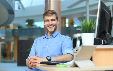 Portrait of happy man sitting at office desk, looking at camera, smiling.