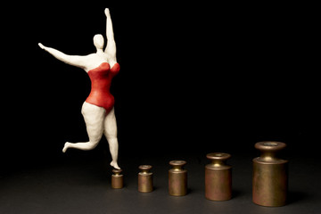 Fat happy woman dancing on a way of weight. Isolated on black background. With copy space text. Studio Shot.