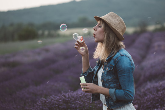 Beautiful woman blowing soap bubble
