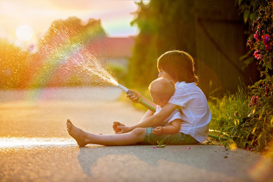 Adorable little children, brothera, playing together with a garden hose on hot and sunny summer day on sunset