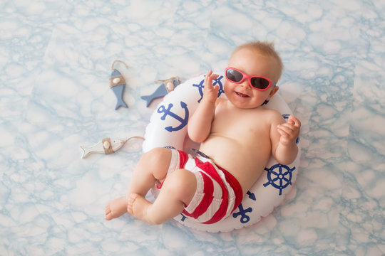 Cute baby boy lying down on a tiny inflatable swim ring,  wearing swimsuit shorts and sunglasses