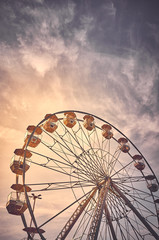 Vintage toned picture of a Ferris wheel at sunrise.