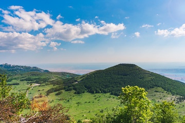A beautiful landscape view over a mountain valley and forested mountain peaks of Velebit mountain range in Croatia of the Adriatic sea or coastline with islands. Summer in Croatia or travel concept