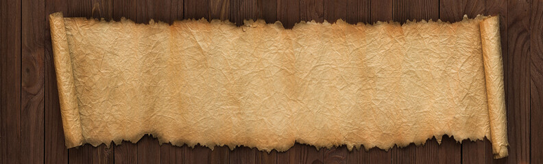 Panoramic background of old paper. Unfolded scroll on the table