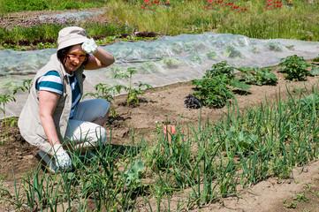 Frau mittleren Alters arbeitet an einem Gemüsebeet in ihrem Garten