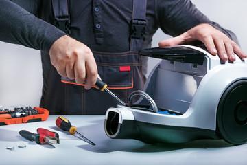 Repairman repairs of vacuum cleaner. Repairing cleaner.Small business.