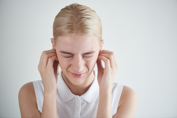 Hearing problems. Girl covers her ears