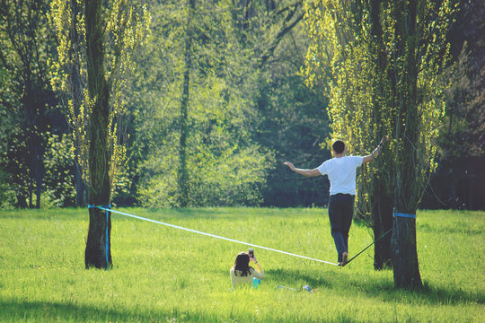 young man walking on a wire, a girl sitting on the green grass shooting the slackling activity with her smartphone