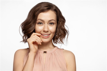 Portrait of elegant young woman in trendy shirt in powder color touching her perfect clean skin. Lovely lady with nice hairstyle and professional make-up looking at camera with happiness