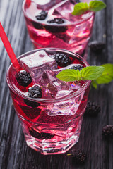 mulberry cocktail with ice and fresh mint on a black wooden table