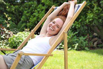Hübsche rotharrige Frau sitzt lachend in einem Liegestuhl