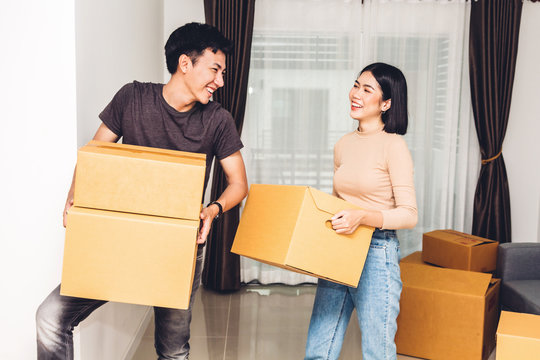 Happy young couple carrying boxes and moving into their new home.House moving and real estate concept