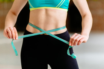 Close up of  woman measuring perfect shape of beautiful waist, healthy lifestyles concept.