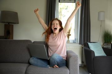 Hübsche rothaarige Frau sitzt mit einem laptop auf ihrem Schoß auf einer Couch und jubelt begeistert