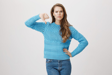 Portrait of beautiful sexy european female holding hand on waist and showing disapproval gesture with thumbs down, expressing disappointment and worry, standing over gray background.