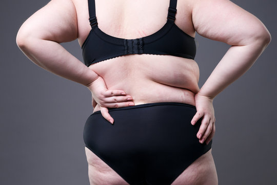 Back pain, fat woman with backache, overweight female body on gray background