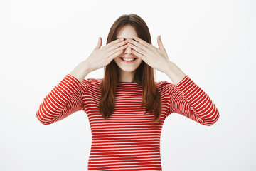 Sister playing hide and seek with teenagers, closing eyes and counting. Joyful happy young woman with brown hair, covering vision with palms and smiling broadly, feeling temptetion while waiting gift