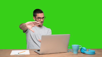 Concentrated young man sitting at his desk doing a gesture of focusing with his hands - Green background