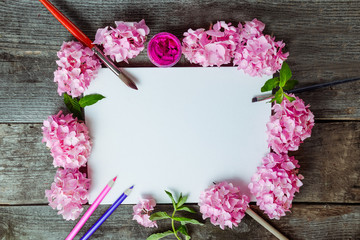 Top view Creative layout made of pink wisteria flowers, canvas blank, brushes, fuchsia color gouache paint, color pencils on the old wooden rustic table. Flat lay. Art concept. Copy space.