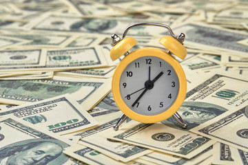 Alarm clock and dollars, close up. Time is money. Yellow alarm clock on money banknotes Dollars, concept of business planning and finance.