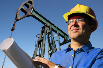 Drilling Engineer Oil & Gas Careers As A Concept /Drilling oil engineer with yellow hard hat and blueprint in an oilfield